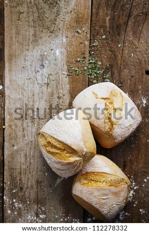 Fresh crusty bread rolls lightly dusted with flour on an old wooden surface with copyspace - stock photo