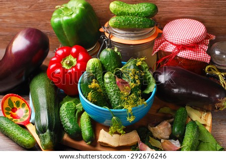 fresh cucumbers,eggplants,courgette and peppers ready for pickles on wooden background - stock photo