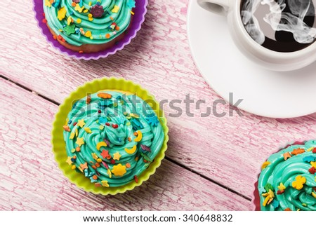 Fresh cupcakes and coffee on the wooden table - stock photo