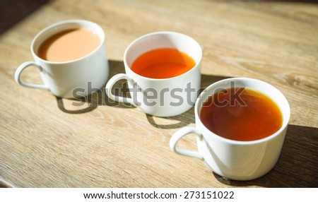 Fresh cups of tea and coffee with shadows of cups on a wooden table - stock photo