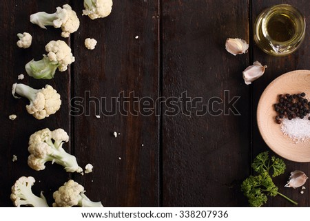 fresh cut cauliflower with ingredients for cooking on rustic wooden background