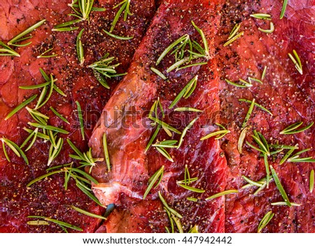 Fresh cut raw juicy beef meat steak seasoned with pepper and rosemary. - stock photo