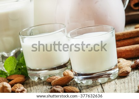 Fresh dairy products and nuts on an old wooden background, selective focus