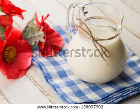 Fresh dairy products - milk in pitcher on wooden table. Rustic style. Bio/organic/natural ingredients. Healthy eating. - stock photo