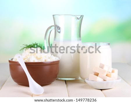 Fresh dairy products on wooden table on natural background