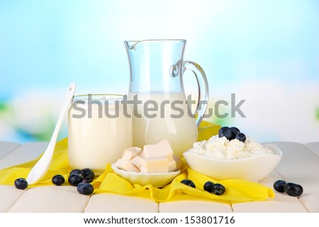 Fresh dairy products with blueberry on wooden table on natural background