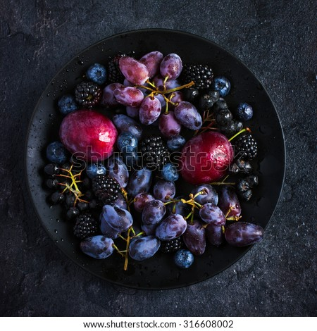 fresh dark fruits and berries on black plate . Top view, square image - stock photo