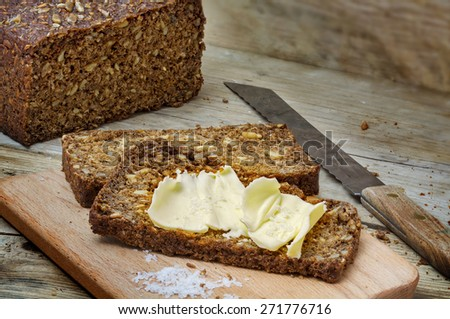 fresh dark rye bread with seeds, butter and salt on rustic wood, copy space - stock photo