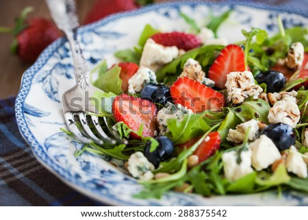 Fresh delicious arugula, strawberry, blueberry, pine nuts and blue cheese salad, soft focus - stock photo