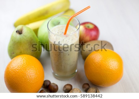 Fresh delicious bright healthy fruit cocktail in a glass on a white background inrgidienty apples oranges bananas pears kiwi nuts