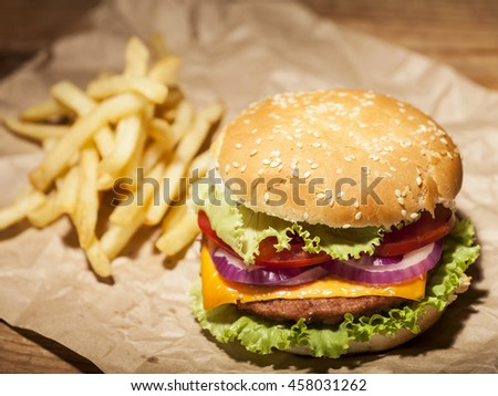 Fresh delicious burger with cheese, tomato, onion, lettuce and french fries on brown paper on wooden table - stock photo