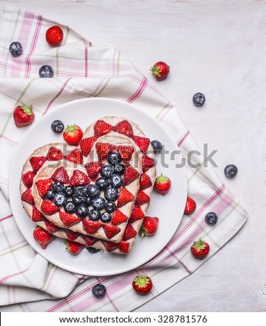 Fresh delicious homemade cake with strawberries and blueberries  In the form of heart In pink and white napkins on rustic wooden background close up top view - stock photo