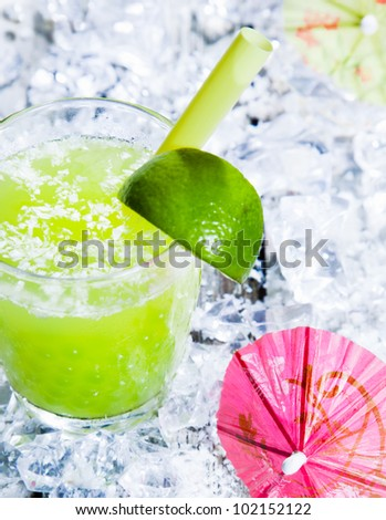 Fresh delicious lime smoothie on a bed of crushed ice with a cocktail umbrella - stock photo