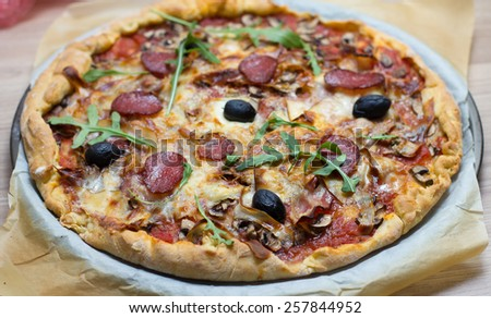 Fresh Delicious Pepperoni Pizza Homemade with black Olive Mushroom and rucola. - stock photo