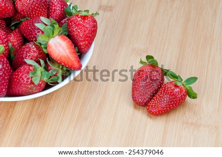 Fresh delicious red Strawberries in a bowl on a wooden surface. Strawberries are with green stems and leaves - stock photo