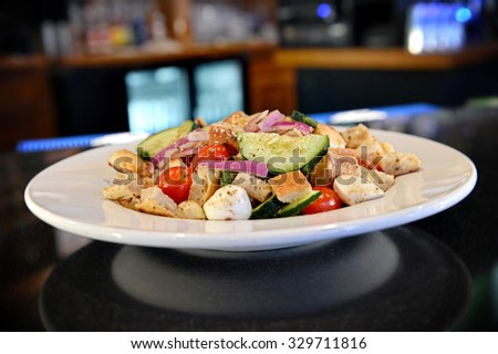 Fresh Dinner Salad with warm croutons, warm ciabatta croutons, fresh mozzarella, cherry tomatoes, English cucumbers, red onions and fresh basil tossed in balsamic vinaigrette. - stock photo