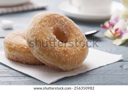 Fresh donut served with a cup of coffee on blue table - stock photo