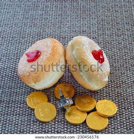 Fresh donuts, silver dreidel and chocolate coins for Hanukkah celebration. - stock photo