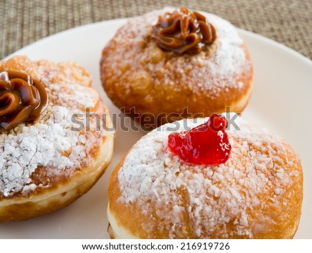 Fresh donuts with jam and chocolate on white plate for Hanukkah celebration. - stock photo