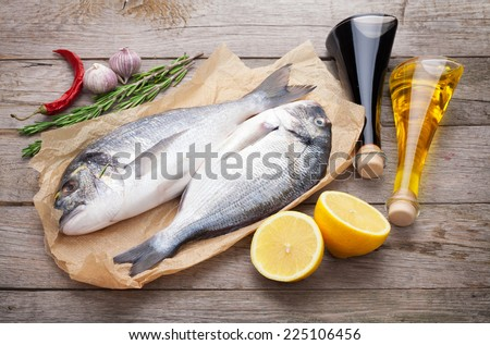 Fresh dorado fish cooking with spices and condiments on wooden table - stock photo