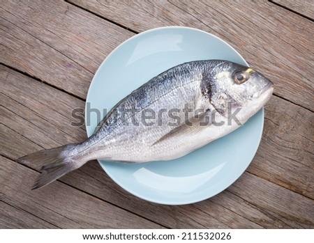 Fresh dorado fish on wooden table - stock photo