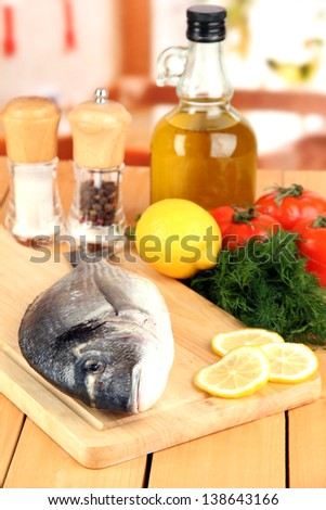 Fresh dorado on chopping board with lemon and vegetables on wooden table