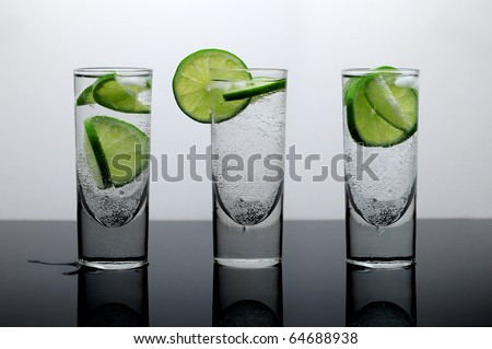 Fresh drink of water with lime and ice in three clear glasses on a reflective surface