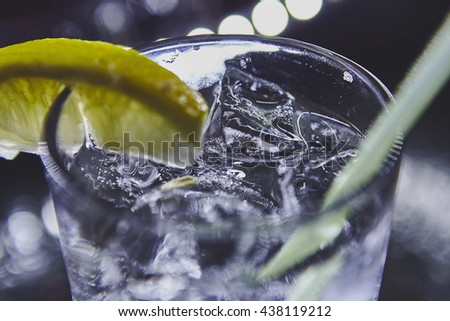 Fresh drink with ice and lime on black background - stock photo