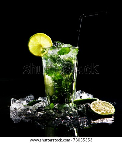 Fresh drink with ice, green mint and lime on black background - stock photo