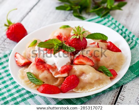 Fresh dumplings with strawberries and sour cream - stock photo