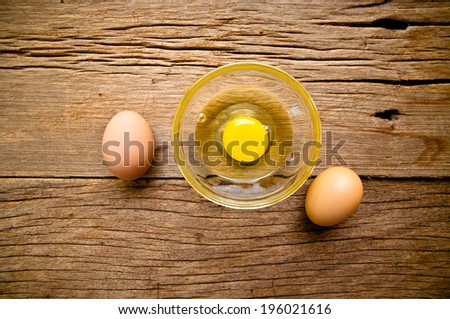 Fresh Egg With Bowl of Egg White on Wooden Table, Food Rustic Style. - stock photo