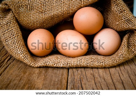 Fresh Egg With Burlap Sack Harvest on Wood Table Background, Food Rustic Still Life Style. Concept and Idea for Homemade Organic Food Art Decoration.