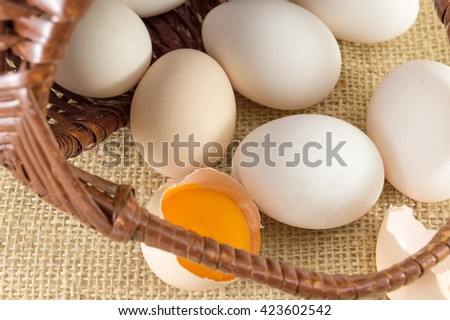 Fresh eggs falling out of awicker basket - stock photo
