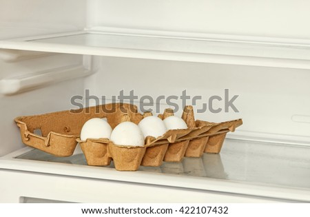 Fresh eggs in a paper box on refrigerator shelf. - stock photo