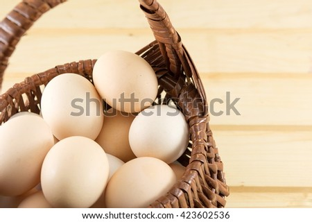 Fresh eggs in a wooden basket - stock photo