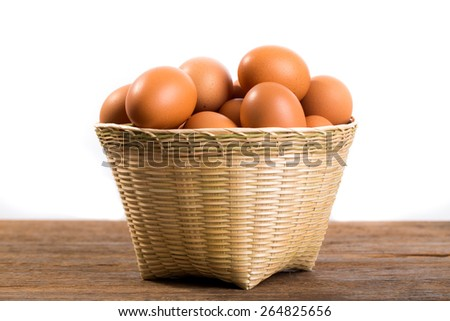 Fresh Eggs in basket on table with white background. - stock photo