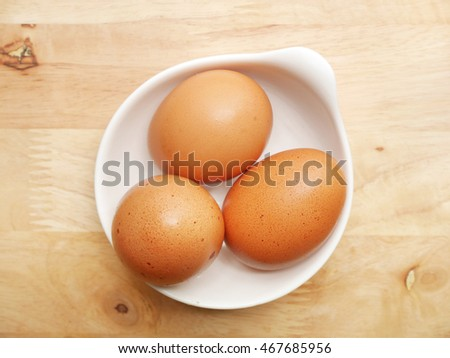 Fresh eggs in bowl on wooden background