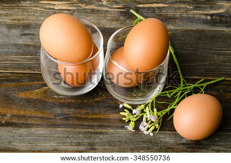 Fresh eggs in the glass on wooden background