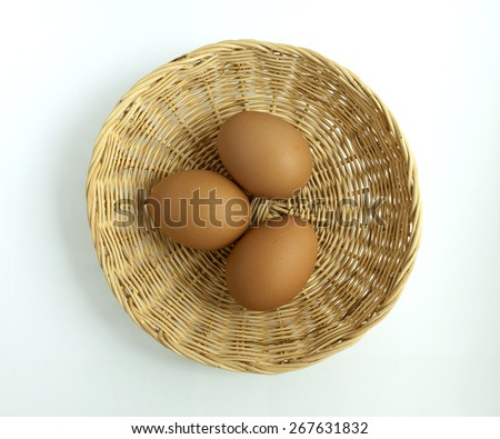 Fresh eggs in the round basket on white background - stock photo