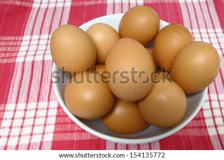 Fresh eggs in white bowl on gingham tablecloth