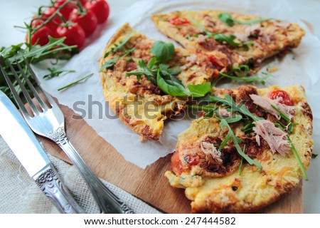Fresh eggs omelet with tomatoes and rucola salad leafs - stock photo