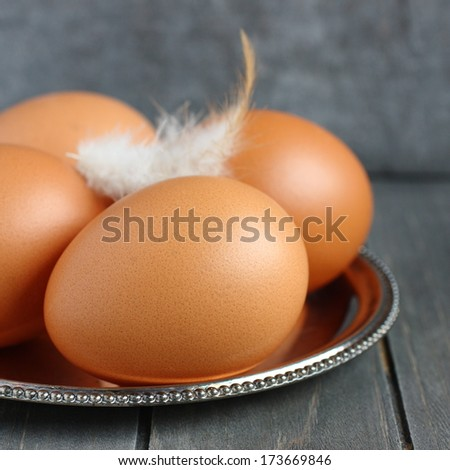 Fresh eggs on metal plate on rustic wooden background - stock photo