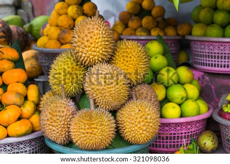 Fresh exotic tropical fruits for sale at an outdoor market. Durians, mandarines, lemons - stock photo