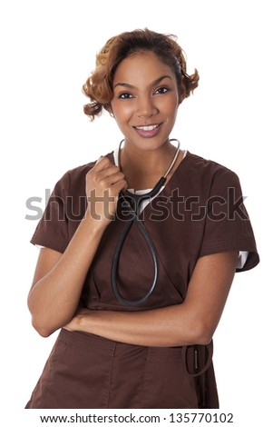 Fresh faced woman smiles while clutching a stethoscope, isolated on white background. - stock photo