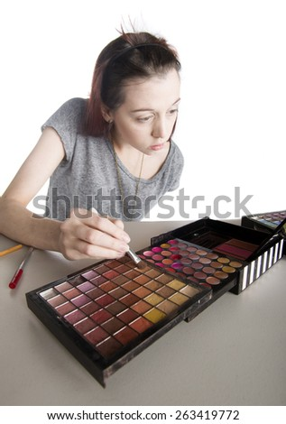 Fresh Faced Young Teenage Woman with Large Palette of Make Up Choosing Shade of Eye Shadow to Apply with Brush