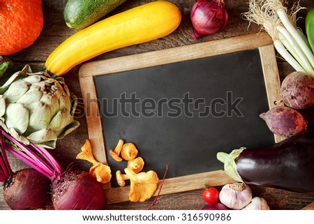 Fresh fall cooking ingredients including mushrooms, beetroot, artichoke, marrow, peppers onion, pumpkin and spring onion around a blank vintage slate with copyspace for your menu or recipe - stock photo