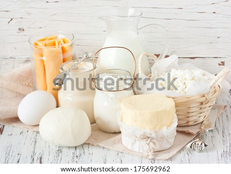 Fresh farm dairy products on a white wooden background. Tasty cheese, butter, eggs, milk and yogurt close-up. - stock photo