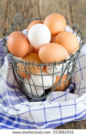 fresh farm eggs in iron basket - stock photo