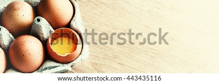 Fresh farm eggs on wooden table background with copy space. Health and diet concept