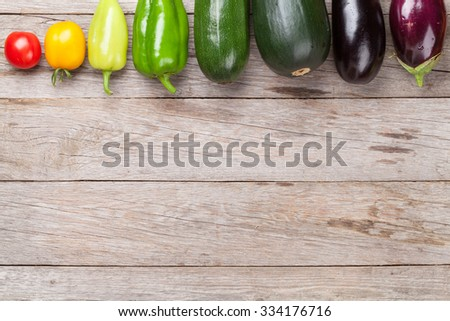 Fresh farmers garden vegetables on wooden table. Top view with copy space - stock photo